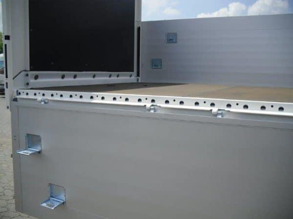 Baustoffanhänger mit runtergeklappter Ladefläche.